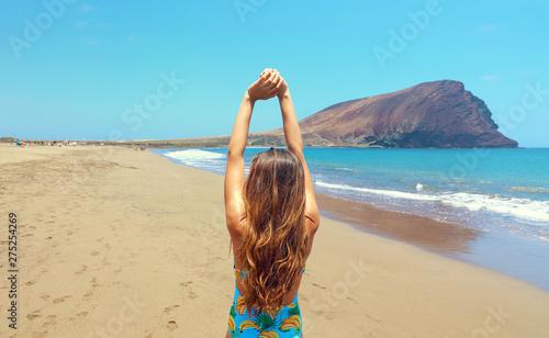 Back view beautiful woman doing stretching exercises on the beach in Playa La Tejita, Tenerife