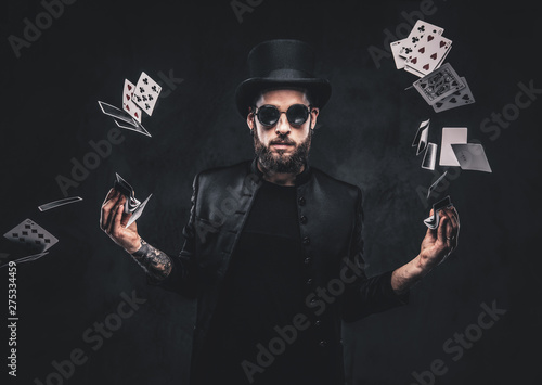 Canvas Print Magician in a black suit, sunglasses and top hat, showing trick with playing cards on a dark background