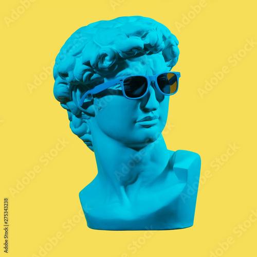 Statue. Earphone. Isolated. Gypsum statue of David's head. Man. Creative. Plaster statue of David's head in blue sunglasses. Minimal concept art.