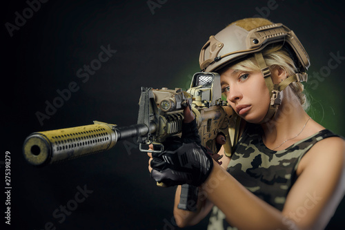 Leinwand Poster the girl in military overalls airsoft posing with a gun in his hands on a dark b