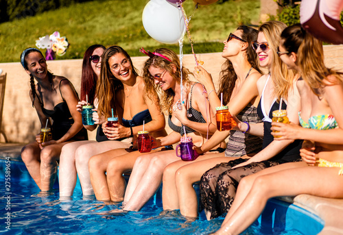 Fotografia Group of girlfriends at a poolside summer party sitting at the edge of a swimming pool drinking and having fun