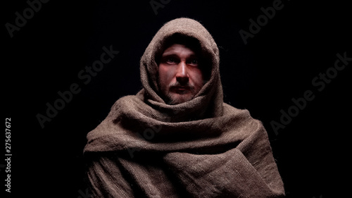 Obraz na plátně Poor male in rough robe looking directly to camera, early christian prophet