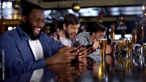 Photo Emotional african-american male celebrating winning bet on match, bookmaker app