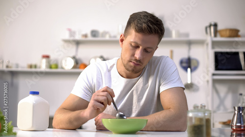 Fotografia Unhappy lonely man looking with disgust at food in bowl, lack of appetite