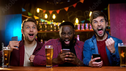 Foto Excited friends rejoicing watching horse race and making bets online, income