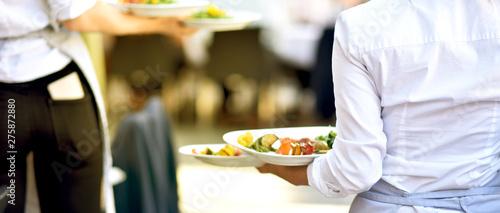 Photographie Bedienung serviert Essen für die Gäste im Restaurant