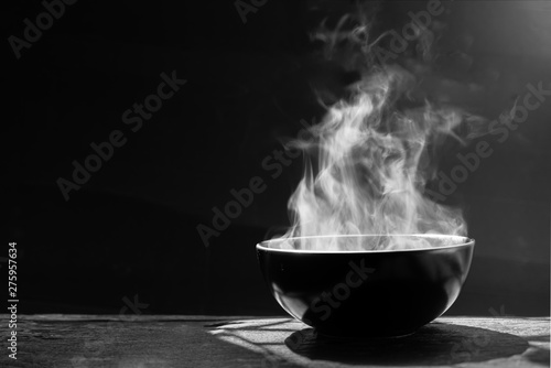 Canvas Print Steam of hot soup with smoke wood bowl on dark background