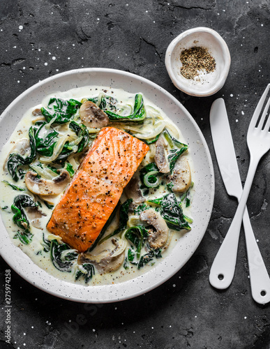 Canvas Print Baked salmon with creamy spinach mushrooms sauce on a dark background, top view
