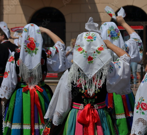 Fotografia girl in traditional costume from Lowicz region in Poalnd stand on their back wav