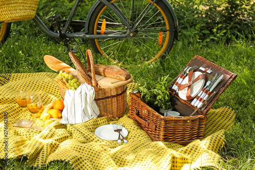 Fotografia Wicker baskets with tasty food and drink for romantic picnic in park