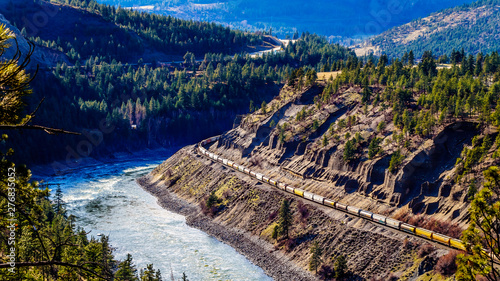 Canvas Print Long Freight Trains following the Thompson and Fraser Rivers along steep Cliffs
