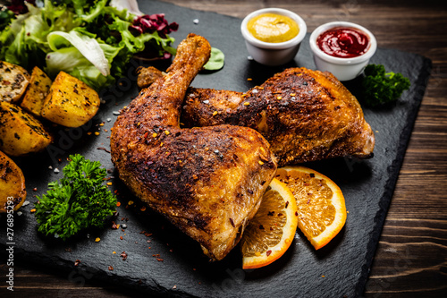 Photographie Roast chicken legs on black stone plate