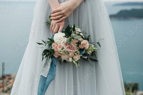 Fotografie, Obraz Close-up bride holds in hands a beautiful wedding bouquet