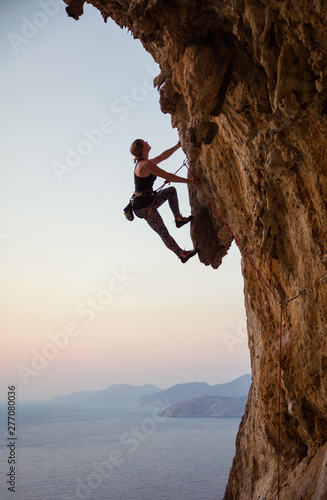 Fotografia Young woman climbing challenging route at sunset