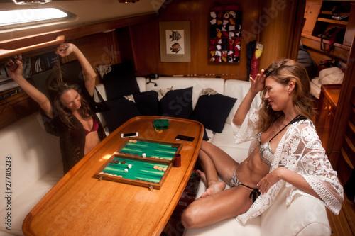 Tela Ragazze che giocano a backgammon sottocoperta a bordo di yacht a vela