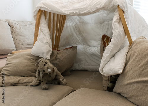Fotografia, Obraz A pillow fort made of blankets chairs with a stuffed animal in the living room