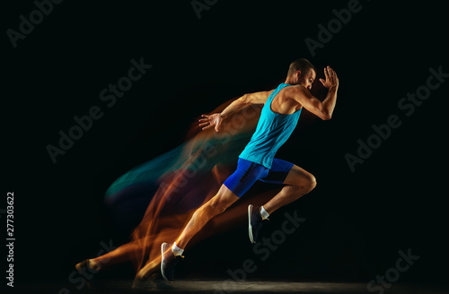 Canvas Print Professional male runner training isolated on black studio background in mixed light