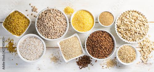 Obraz na płótnie Selection of whole grains in white bowls - rice, oats, buckwheat, bulgur, porrid