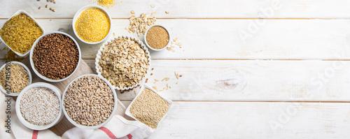 Foto Selection of whole grains in white bowls - rice, oats, buckwheat, bulgur, porrid