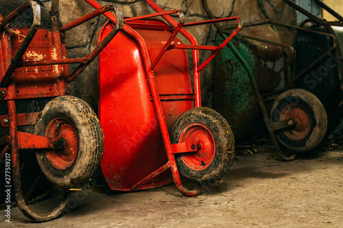 Photographie Farm stable wheelbarrows leaning on to wall