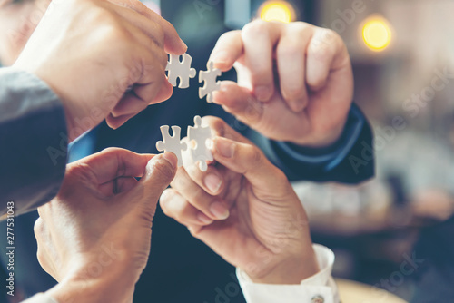 Fotografie, Obraz Businessman team work holding two jigsaw connecting couple puzzle piece for matching to goals target, success and start up new project in office, select focus