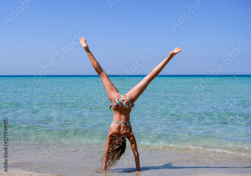 Fotografie, Obraz Slim and athletic girl doing a handstand before a wonderful beach with crystal c