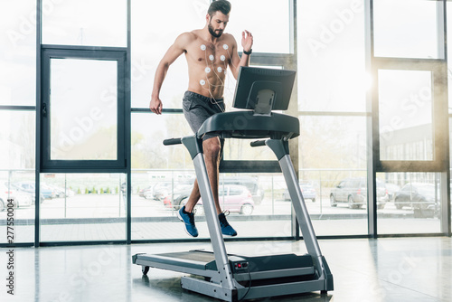 handsome sportsman with electrodes running on treadmill during endurance test in Fototapeta