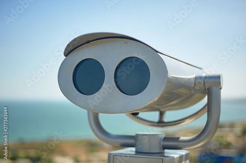 Fotografia Binoculars on the observation deck overlooking the sea.