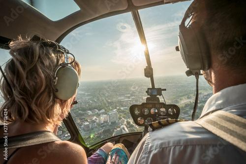 Fototapeta Portrait of beautiful blonde women and pilot enjoying helicopter flight