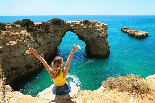 Fotografia Young beautiful woman enjoying the panoramic top view of rocky beaches with cliffs somwhere, somwhere in Algarve, Portugal