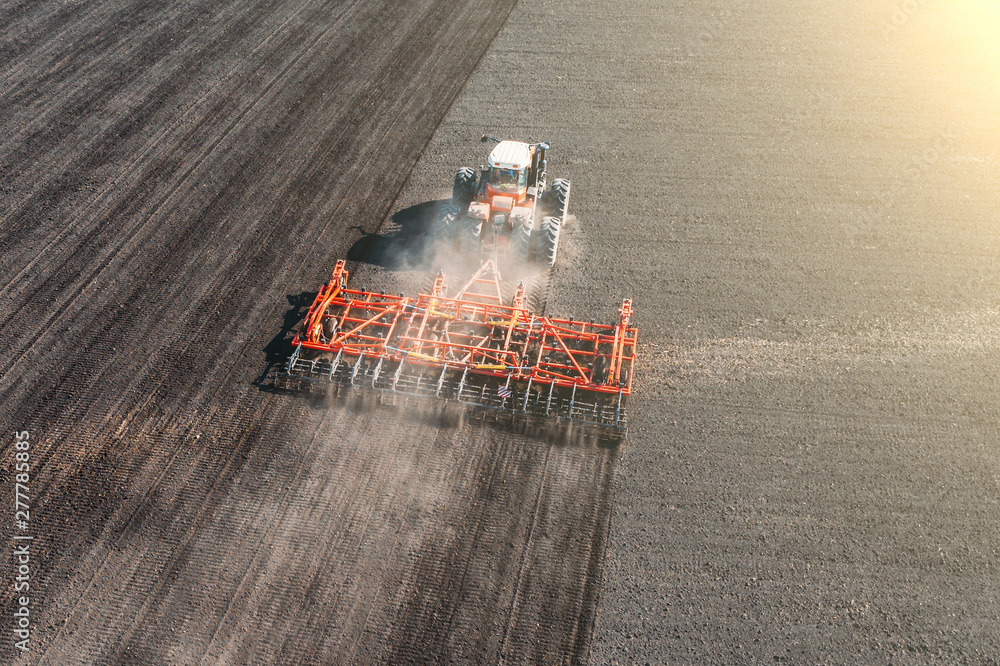 Top view of agricultural industrial tractor plows soil field for sowing , aerial view. Land cultivation <span>plik: #277785885   autor: DedMityay</span>