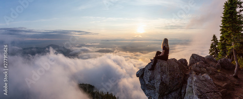 Photographie Adventurous Female Hiker on top of a mountain covered in clouds during a vibrant summer sunset