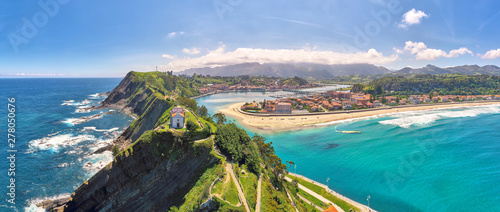 Aerial panorama of a church on top of the cliffs, views of the beach and mountains on the background
