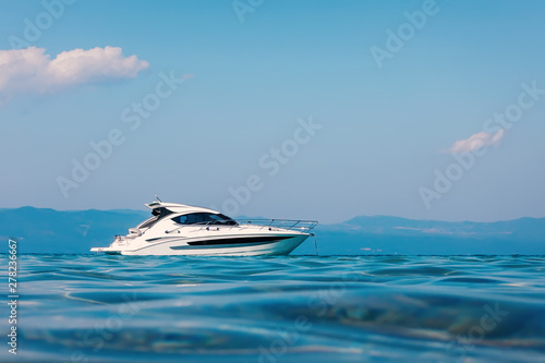 Fotografia Motor boat floating on clear turquoise water