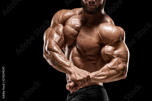 Foto Muscular man showing muscles and biceps isolated on the black background