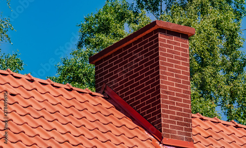 Fotografia Chimney on the roof covered with red tiles