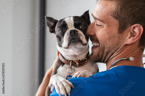 Vet cuddling pet dog
