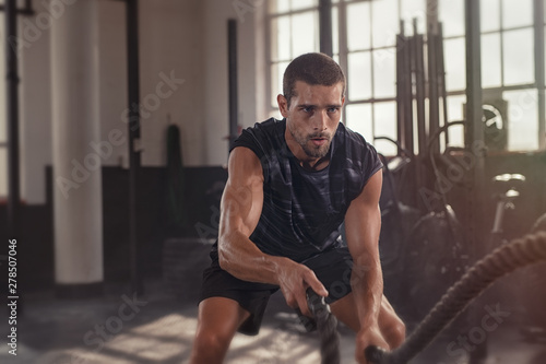 Man doing crossfit exercise with rope