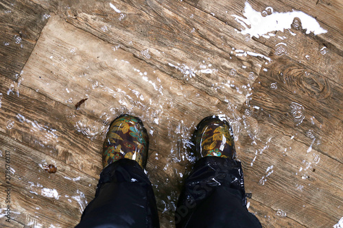 Canvastavla Woman's Feet Wearing Waterproof Boots, Standing in a Flooded House with Vinyl Wood Floors