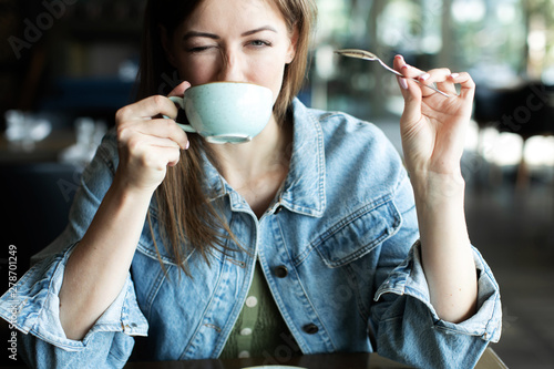 Tableau sur Toile young woman drinking coffee smiling and winking at