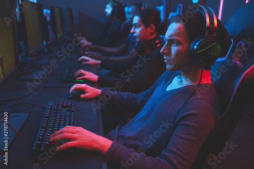 Obraz na plátně Serious concentrated esports player concentrated on game wearing wired headset s
