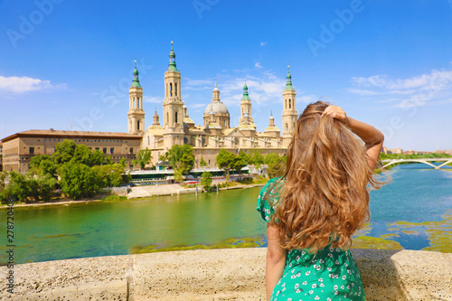 Amazing back view of attractive beautiful woman looking at Cathedral Basilica of Our Lady of the Pillar in Zaragoza, Spain