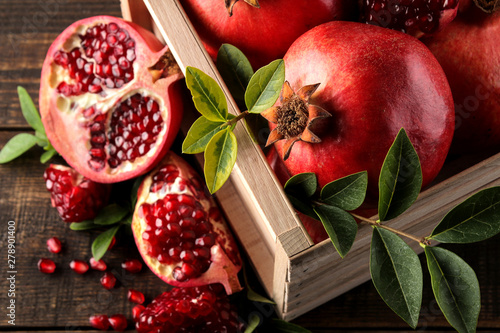 Ripe tasty red pomegranate fruit with leaves in a wooden box on a brown wooden table. top view