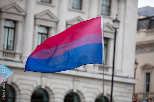 Canvas Print A bisexual flag is waved in the air at a pride event