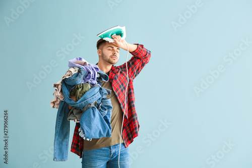 Stampa su Tela Stressed young man with iron and clothes on grey background