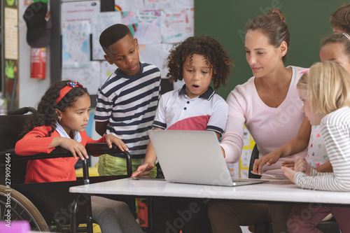 Canvas Print Teacher and school kids discussing over laptop in classroom