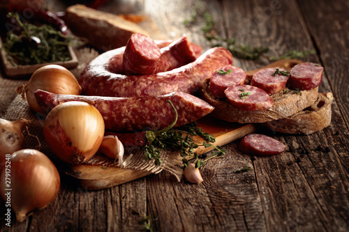 Wallpaper Mural Dry-cured sausage with bread and spices on a old wooden table.