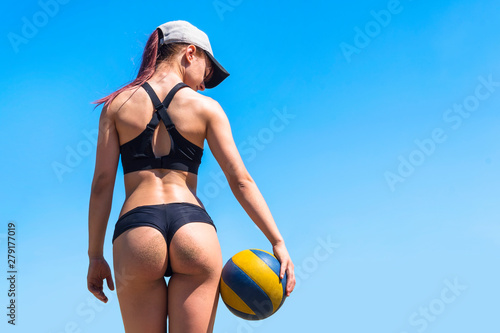 beautiful young woman stands with her back with a volleyball in her hands in a sports black swimsuit on a blue sky background. view from the back. concept of a healthy lifestyle. Beach volleyball.