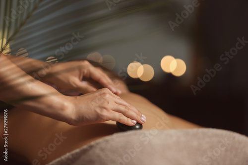 Beautiful young woman undergoing treatment with hot stones in spa salon