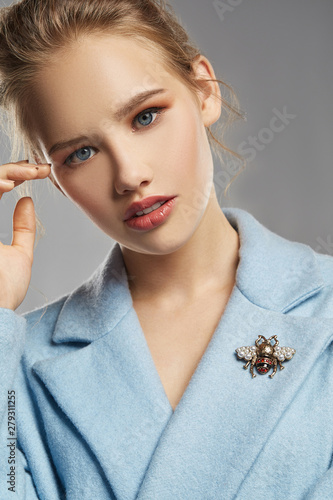 Foto Portrait of lady, wearing sky blue coat with brooch in view of bee with contrasting stripes and wings covered with pearls